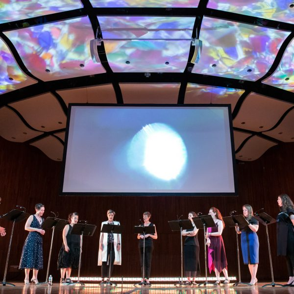 Nine women (lorelei ensemble) sing on a stage while multicolored projections float on the ceiling and a moon-like shape is projected on a screen behind them